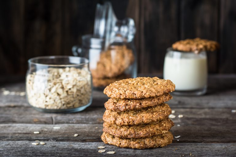 Homemade oatmeal cookies on wooden board on old table background. Healthy Food Snack Concept. Copy space. Milk and cookies. Still life of food. Vegetarian food. Healthy food. Breakfast concept.